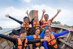 Traveler group that are large family enjoy on the boat. Traveler group that are large family in life vest raise hands with happy and enjoy on the boat while stock photo