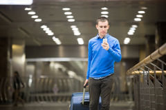 Traveler guy using phone at airport. Portrait of young handsome guy wearing casual style clothes walking in modern station. Traveler making call using smartphone Royalty Free Stock Photos