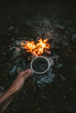 Traveler hand holding cup of coffee above the campfire Stock Photography
