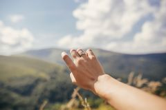 Traveler hand reaching out to mountains with engagement ring. gi. Rl hand on background of sunny mountains and sky. travel and wanderlust concept. summer stock photo