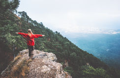 Traveler hands raised standing on mountains cliff Stock Images