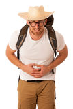 Traveler having stomach ache, nausea wearing straw hat, white sh. Irt and backpack. Isolated over white Royalty Free Stock Photography