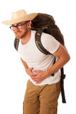 Traveler having stomach ache, nausea wearing straw hat, white sh. Irt and backpack. Isolated over white Royalty Free Stock Photos