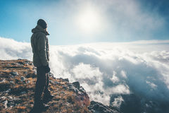 Traveler hiking on mountain cliff over clouds Stock Image