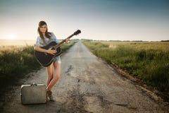 Hippie girl on road. Traveler hippie girl with guitar stock photos