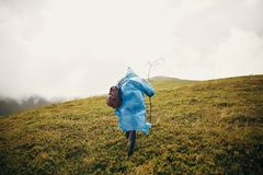 Traveler hipster girl in blue raincoat with backpack, exploring. Misty mountains. space for text. atmospheric moment. travel and wanderlust concept.  woman Royalty Free Stock Images