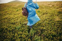 Traveler hipster girl in blue raincoat with backpack, exploring. Misty mountains. space for text. atmospheric moment. travel and wanderlust concept.  woman Stock Photography