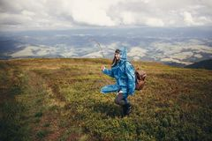 Traveler hipster girl in blue raincoat with backpack, exploring. Misty mountains. space for text. atmospheric moment. travel and wanderlust concept.  woman Royalty Free Stock Photography