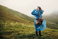 Traveler hipster girl in blue raincoat with backpack, exploring. Misty mountains. space for text. atmospheric moment. travel and wanderlust concept.  woman Royalty Free Stock Photos