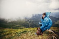Traveler hipster girl in blue raincoat with backpack, exploring. Misty mountains. space for text. atmospheric moment.  woman sitting on top hill. travel and Royalty Free Stock Photo