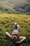 Traveler hipster girl in hat lying on grass in sunny mountains a. Nd relaxing. summer vacation. space for text. happy atmospheric moment. woman resting. travel Royalty Free Stock Photo