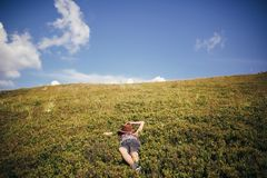 Traveler hipster girl in hat lying on grass in sunny mountains a. Nd relaxing. summer vacation. space for text. happy atmospheric moment. woman resting. travel Stock Photos