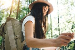 Traveler hipster woman with backpack and hat hold in hands location map and searching directional among trees in forest Stock Images