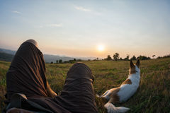 Traveler and his dog sitting in the grass and watching the sunse Royalty Free Stock Photos