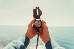 Traveler holding a compass on background of sea Royalty Free Stock Photography
