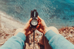 Traveler holding a compass on coastline Stock Photo