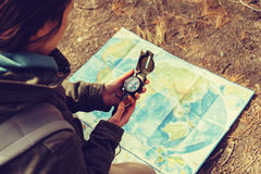 Traveler holding a compass in the forest. Traveler young woman searching direction with a compass on background of map outdoor. Image with instagram color effect Stock Photography