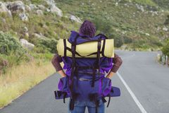 Traveler holding hicking bag on the road. Digital composite of traveler holding hicking bag on the road Royalty Free Stock Photo