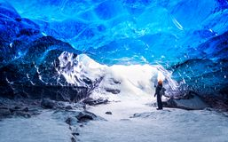 Traveler in ice cave. Man standing underground inside of a glacier, climate specific, Vatnajokull National Park, amazing nature of Skaftafell, Iceland Stock Image