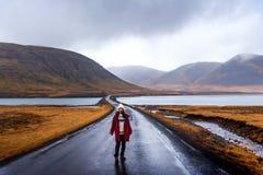 Traveler on Icelandic road in Snaefellsnes peninsula of Iceland. Traveler on scenic Icelandic road in Snaefellsnes peninsula of Iceland woman icelad female girl royalty free stock photography