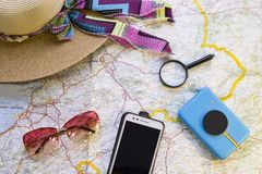 Traveler items on a map. A straw hat, a mobile phone, sunglasses, a camera and a magnifying glass. Travel concept mock up Stock Photo