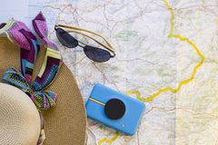 Traveler items on a map. A straw hat, sunglasses, a camera and a magnifying glass. Travel concept mock up. Top view Royalty Free Stock Photography