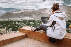 Traveler with laptop sits on top view point on the mountain vall Royalty Free Stock Photo