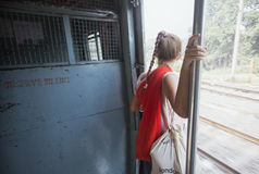 Traveler leans out train in India Stock Photo