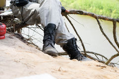 Traveler in leather boots sit over a cliff above the river near Stock Photos