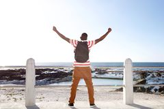 Traveler looking at the beach with  arms raised. Portrait from behind of young african man traveler standing with arms raised and looking at the beach Royalty Free Stock Photos