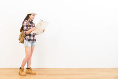 Traveler looking for travel route happily with map. Smiling female traveler standing on wooden floor looking at paper map looking for travel route happily with Royalty Free Stock Photos