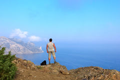 Traveler looks at the beautiful seascape from the mountain top. Traveler looks at the beautiful Crimean seascape from the top of the mountain, the mountain stock photos