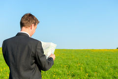 Traveler lost  with a map. Traveler lost in a jacket with a map Royalty Free Stock Photo