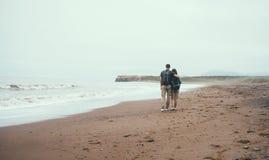 Traveler loving couple walking on beach near the sea. Traveler loving couple with backpacks walking on beach near the sea in summer. Man embracing a woman, rear Royalty Free Stock Photos