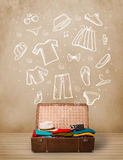 Traveler luggage with hand drawn clothes and icons. On grungy background Stock Photo