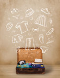 Traveler luggage with hand drawn clothes and icons. On grungy background Stock Image