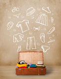 Traveler luggage with hand drawn clothes and icons. On grungy background Royalty Free Stock Photo