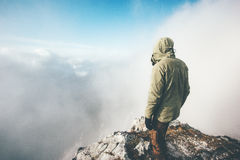 Traveler man alone on mountain summit over clouds Royalty Free Stock Images