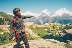 Traveler Man with backpack hand showing destination. Travel Lifestyle concept serene view mountains landscape on background adventure vacations outdoor royalty free stock photo