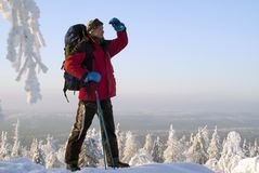 The traveler looks away from the top of the mountain in winter. Traveler man with a backpack looking into the distance from under the arm, standing on top of the Stock Image