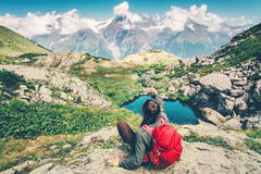 Traveler Man with backpack relaxing hand showing. Destination Travel Lifestyle concept serene view mountains and clouds landscape on background summer vacations Stock Photo