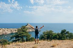 Traveler man with backpack standing with raised hands on the nature. Symbolizes freedom, solitude and unity with nature Royalty Free Stock Image