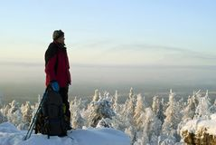 A traveler on top of a winter mountain admires the scenery Royalty Free Stock Images