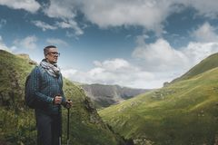 Traveler Man With Backpack And Trekking Poles Resting And Looking At The Mountains In Summer Outdoor royalty free stock photography