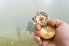 Traveler man with compass seeking a right way through the fog Royalty Free Stock Images