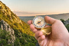 Traveler man with compass seeking a right way in the mountains Stock Photos