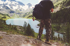 Traveler Man enjoying lake and mountains view. Travel Lifestyle concept adventure summer vacations outdoor wayfarer with backpack Royalty Free Stock Images