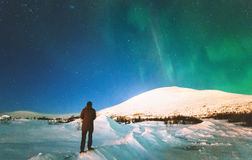 Traveler man enjoying Northern lights view. Above mountains Travel Lifestyle emotional concept vacations into the wild night scene Stock Photo