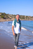 Traveler man  goes on seashore, smiling Royalty Free Stock Photo