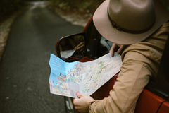 Traveler  man with hat  looking map near car in autumn forest Stock Image